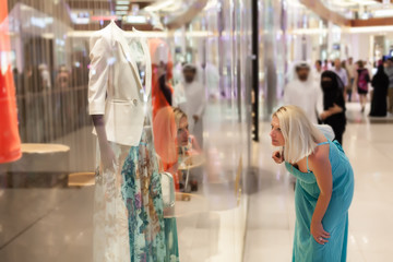 Beautiful mid age woman looking about the merchandise.Soft focus, shallow doff , Dubai shopping mall