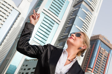 Businesswoman pointing on the skyscraper, city scape Dubai in the background