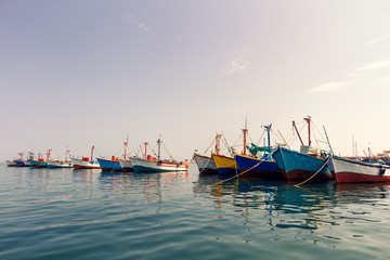 Colorful fishing boats anchored at the pier of Paracas, Peru