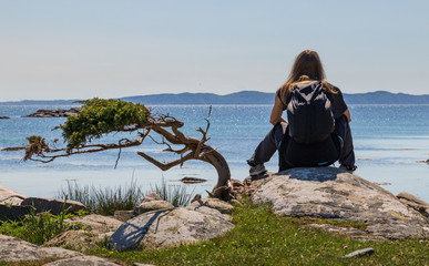 Girl sitting and looking at the ocean in the small island of Hallands Väderö in southern Sweden.