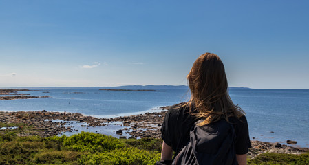 Woman standing and looking at the ocean on Hallands Vadero island in southern Sweden during summer.