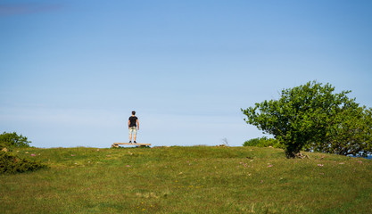 Person standing on a bench looking out over the ocean in the island of Hallands Väderö in southern Sweden.