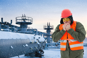 Worker at the cold oil field , natural gas storage in the background.Refinery, oil and natural gas, wintertime