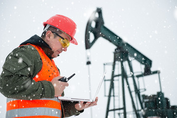 Oil Drill, oil and gas field ,pump jack,  snow storm and worker.