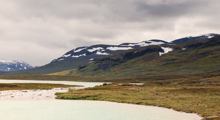 Row of people walking a trail during the hike of Kungsleden (Kings path) in northern Sweden.