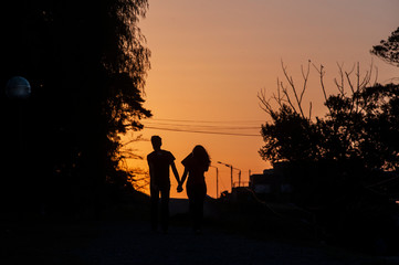 Walking couple silhouette in the sierra at sunset