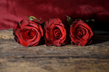 Three red roses on vintage background