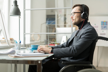 Side view of serious businessman in headphones sitting in wheelchair and typing on computer at the office desk