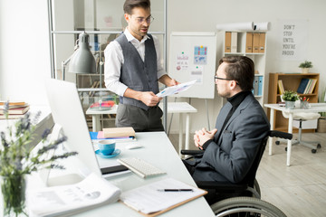 Businessman holding documents and discussing it with his disabled colleague who is sitting in wheelchair at office
