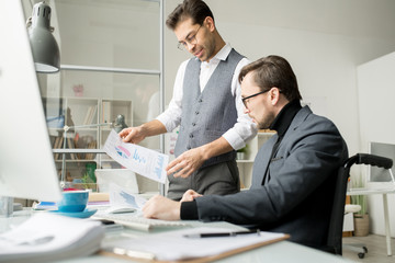 Confident employee holding document with charts and graphs and showing work results and company growth to his male leader