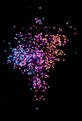 Multicolor bokeh lights, tiny hearts on a black background, top view, carnival, night party invitation or festive background, starry night sky