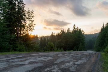 fantastic and wonderful sunset in the mountains, road, forest colored sky and incredible nature