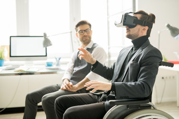 Disabled young man testing wearing goggles and testing virtual reality under the supervision of a professional