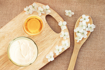 Natural skincare body butter cream, glass jar with honey, fresh blossom top view canvas wooden board background, preparation diy cosmetics healthy lifestyle