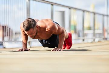 Athletic man doing push up exercise while training outdoors