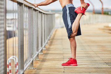 Closeup of man doing stretching exercise outdoors