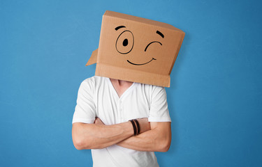 Young man standing and gesturing with a cardboard box on his head with drawn smiley face
