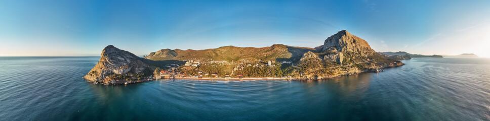Sunset near the village Novyi Svit New light . City district Sudak, the Republic of Crimea. Aerial view. Panorama