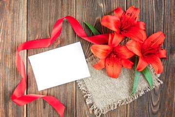 Red lilies with red ribbon and white paper blank on dark wooden background. Holidays card.