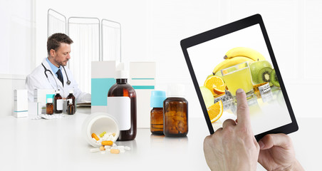 healthy eating and diet concept, hand pointing fruits on digital tablet screen, doctor in medical office desk with pills, bottle tablets and supplements