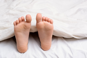 Pair of little girl`s feet in a bed. Small girl sleeps in a bed and her bare feet are visible from under the blanket