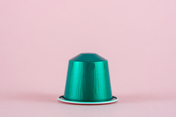 Green Coffee Capsule for compatible systems, espresso coffee,  on pink background.