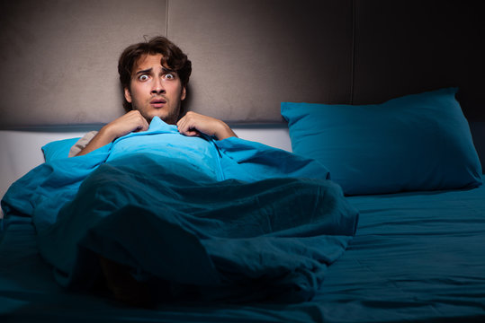 Young man scared in his bed having nightmares