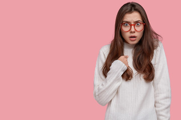 Do you blame me? Dissatisfied female model with indignant facial expression, asks question and points at herself, dressed in white casual oversized sweater, isolated over pink wall with free space