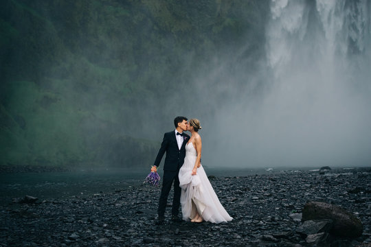 Young happy wedding couple kissing on background of waterfall, outdoors