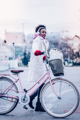 Cute brunette woman walking with her bicycle