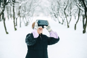girl in glasses of virtual reality walks through the winter snow-covered park