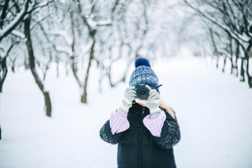 young girl photographer in the winter snowy park photographs nature.