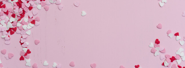 Panoramic website banner image with many tiny heart-shaped sugar sprinkles in red, white and pink with space for copy text or romantic love message for Valentine's Day on February 14th, flat lay