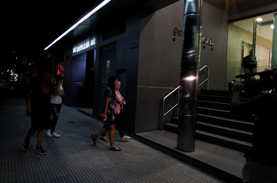 People walk in front of the clinic where Diego Maradona was admitted to undergo a procedure due to stomach bleeding in Buenos Aires