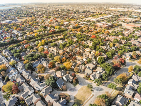 Aerial drone view urban sprawl in suburban Dallas, Texas during fall season with colorful leaves. Flyover subdivision with row of single-family detached houses and apartment complex