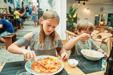 Two funny kids having lunch in the restaurant, eating ravioli and pasta