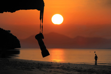 Silhouette of Camera hanging on the rocks along the beach with red sky sunset