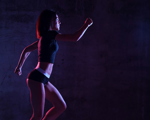 Young sport woman running jogging in gyn in blue and pink neon light on dark wall