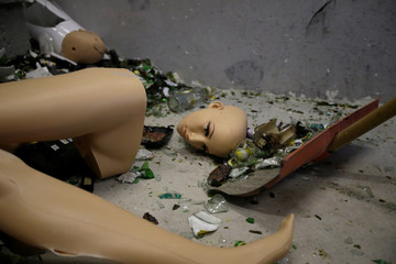 A staff member cleans up a mannequin destroyed by customers in an anger room in Beijing