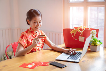 Happy chinese woman wearing a qipao dress traditional or cheongsam and buying online with a red credit card at home.