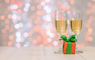 Pair glass of champagne with gift box on festive background with copy space for your text. Valentine day concept