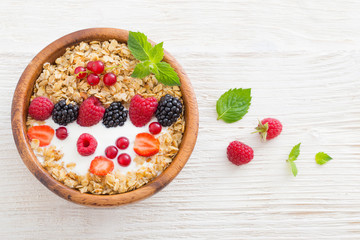 granola with berries on white wooden background