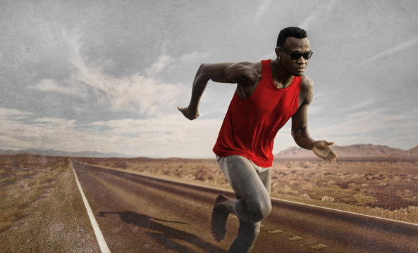 advertising style portrait of young attractive and fit black African American runner man with athletic body doing running workout on asphalt road sprinting hard