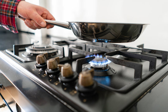 A man cooks in a frying pan, puts it on the stove. Modern gas burner and hob on a kitchen range. Dark black color and wooden Small kitchen in a modern apartment