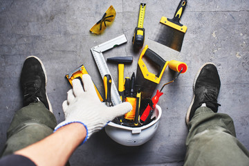 The concept of repair. Male hand reaching for construction tools. First person view.