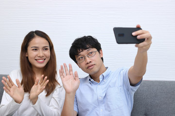 Attractive young Asian couple taking a photo or selfie together in living room. Love and romance people concept.