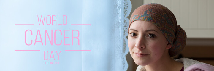 World Cancer Day Banner. Young positive adult female cancer patient sitting in the kitchen by a window, smiling and looking at the camera.