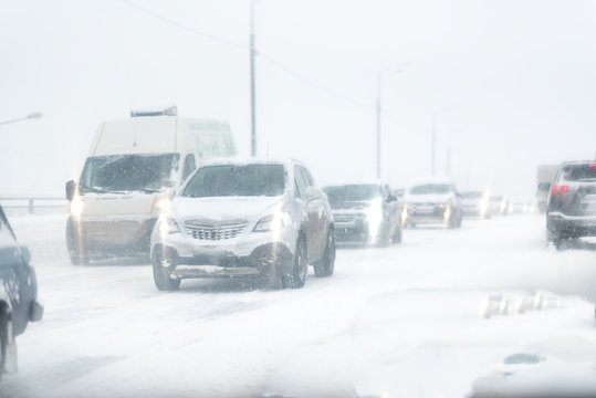 dangerous winter road conditions on a highway with oncoming traffic during heavy snowfall