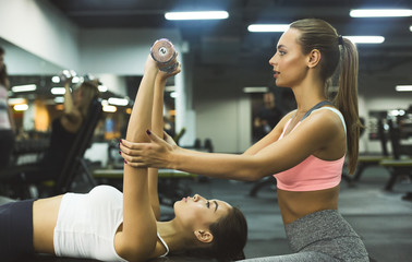 Personal instructor helping woman with chest workout