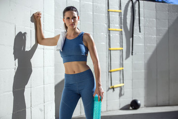 Serious strong confident look from female athlete, next to concrete wall